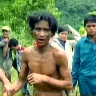 Saattajat taluttavat nuorempaa miestä pois viidakosta.
