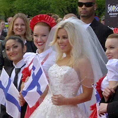 Krista Siegfrieds ja muu Suomen delegaatio Euroviisujen avajaisseremonian punaisella matolla.