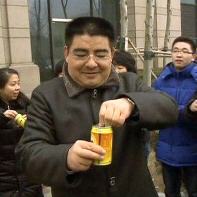 Pullotettua puhdasta ilmaa myyvä Chen Guangbiao ja hänen asiakkaitaan avaamassa pullotettua ilmaa sisältäviä tölkkejä.