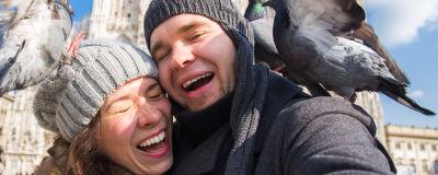 man och kvinna tar ett självporträtt, skrattar då de attackeras av duvor