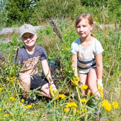 Två barn i ett dike med en sopsäck i handen.