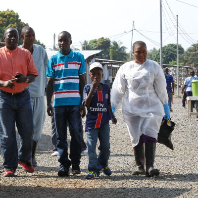 Nathan Gbotoe och hans son Abraham ( i mitten) smittades av ebola men överlevde. Här lämnar de sjukhuset i Liberia i december
