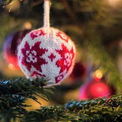 Närbild på en stickad boll i en julgran.