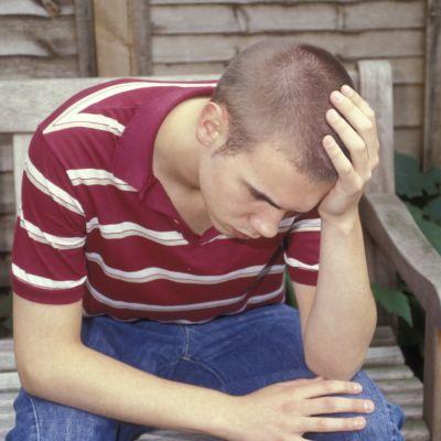 En tonårig pojke sitter på en bänk och ser mycket oroad ut. Han har på sig jeans och en randig t-skjorta.