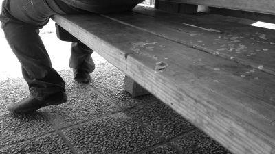 Man sitter på ändan av en bänk