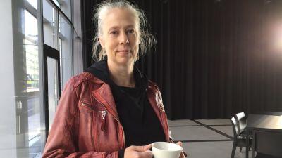 Kvinna med kopp kaffe i handen.