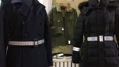 Två kappor med reflexbälten, två reflexbälten på en bänk och en jacka med fastsydda små reflex.