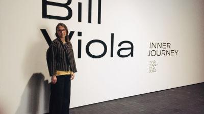 Kvinna framför vit vägg med texten Bill Viola.