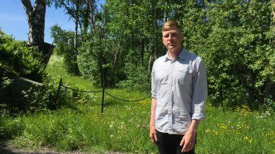 En man står framför en grönskande bakgrund.