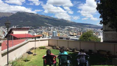 Utsikt från taket på en skola i Ecuador. I bakgrunden reser sig berg mot en blå himmel.