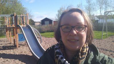 Sofia Sandin-Andersson står leende omt kameran. I bakgrunden ser man en lekplats.