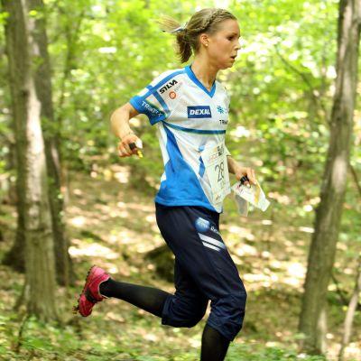 Orienteraren Kirsi Nurmi springer i lövskog.