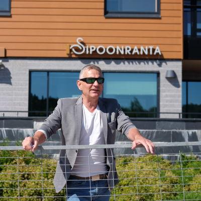 Ben Fuchs står bakom ett metallstaket framför Sibbostrand.
