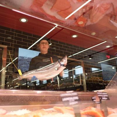 Lotta Lassas står och håller i en lax bakom fiskdisken.