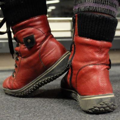Ett par fötter med röda skor inomhus.
