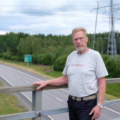 En man ståd vid ett broräcke, bron går över en motorväg.