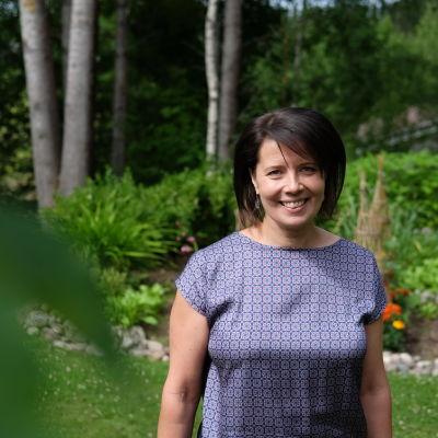 Hanne Aho står i sin trädgård.