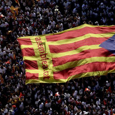 Tuhannet osoittivat tukivat Katalonian itsenäisyyttä alueen epävirallisena kansallispäivänä 11.9. Barcelonassa. Kuvassa ilmasta kuvattu valtava ihmisjoukko kantaa jättikokoista Katalonian lippua.