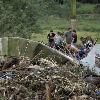 Kuvassa ihmisiä, jotka etsivät uhreja myrskyn tuhoalueella romun keskeltä.