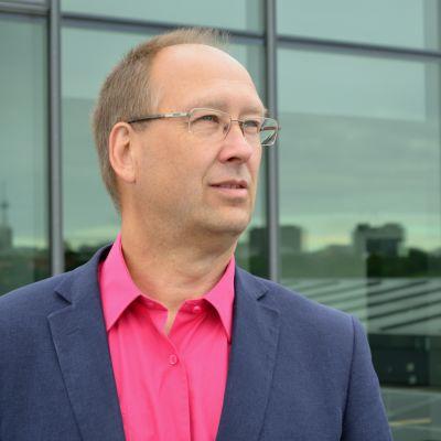 En man i kostym och skjorta utan slips blickar bort åt fjärran. I bakgrunden syns en reflektion av tak i fönster.