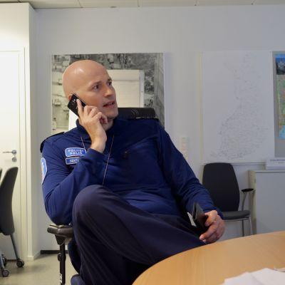 En man i finsk polisuniform sitter inomhus vid ett konferensbord och talar i mobiltelefon.