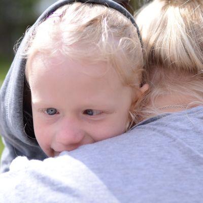 barn med funktionsnedättning i sin famnen på en vuxen