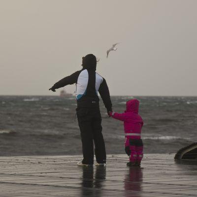 Förälder och barn står vid en brygga och ser på stormen.