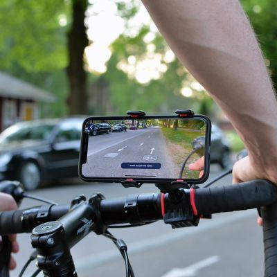 Pyöräilijä polkee pyörää ja katselee sovellusta