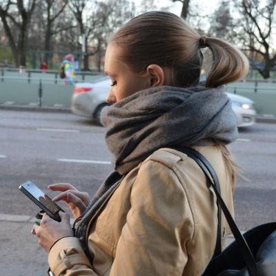 Kvinna går på stan och kollar på sin smarttelefon.