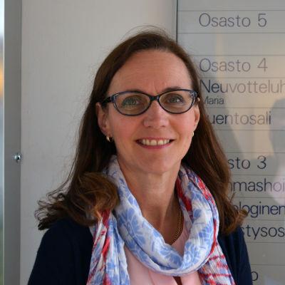 Porträttbild på kvinna i 40-årsåldern som står i en korridor i sjukhusmiljö.