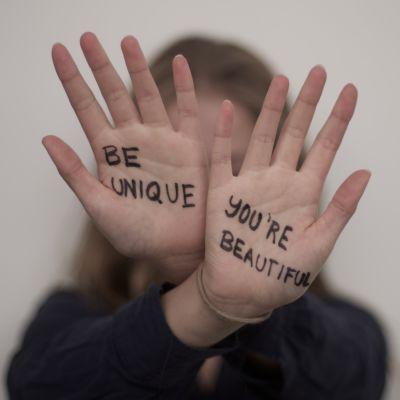 """Två händer som hålls upp med texten """"be unique"""" och """"you're beautiful"""" skrivna på handflatorna."""
