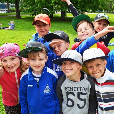 En grupp glada barn i en park.