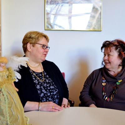 Diakonissorna Barbro Ollberg och Karin Salenius samtalar. Statyett föreställande ängel som dekoration på bordet framför dem.