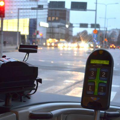Utsikten ur en buss framruta i en korsning.
