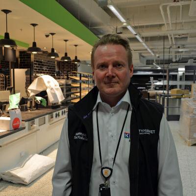 Köpmannen Toni Pokela i sin färdigt inredda mataffär med tomma hyllor.