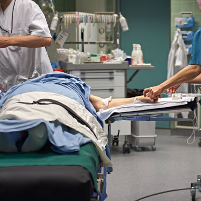 En patient ligger på en säng i en operationssal. Runtom står vårdpersonal.