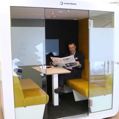 Man läser tidning i ett tyst rum.