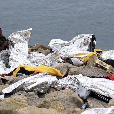 En migrant som skyddar sig med en nödfilt vaknar upp på klipporna i Ventimiglia, Italien, nära den franska gränsen. Fransk polis vägrade släppa in migranterna som försökte komma in i landet.