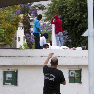 Afrikanska migranter sover i en park i Tel Aviv