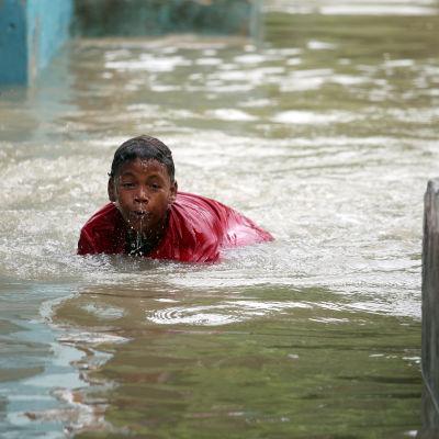 Pojke simmar i vattenmassor efter översvämningar i Santo Domingo, Dominikanska republiken 4.10.2016