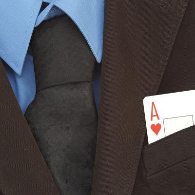 Kostymklädd person med ett ess i jackfickan.