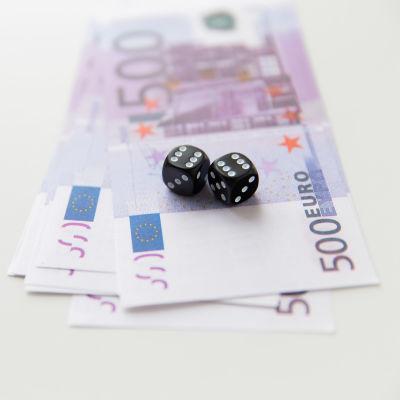 Svarta speltärningar ovanpå en bunt med 500-eurossedlar.