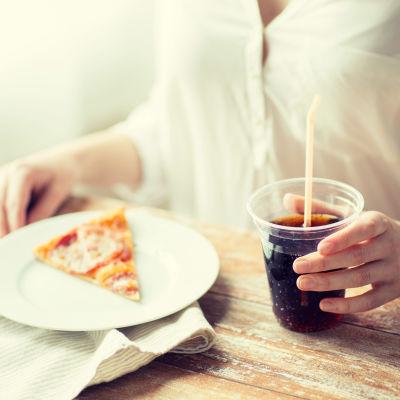 En kvinna äter pizza och dricker coca cola.