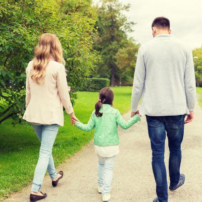 Familj som promenerar i park.