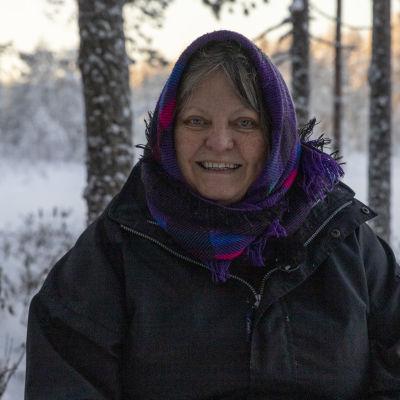 Ekopsykologi Irma Heiskanen hymyilee puiden keskellä