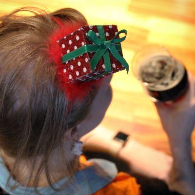 Nainen,jolla on päässään jouluinen koriste, pitelee kädessään olutlasia.
