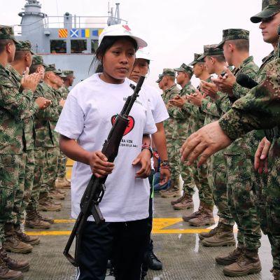 kvinna från rebellgruppen ELN ger över sitt vapen till militären