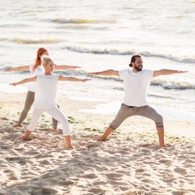 Grupp som yogar i vita kläder på en strand