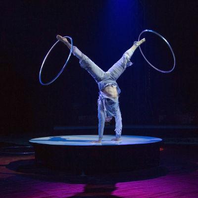 Anton Monastyrsky esittää hulavannenumeroa Sirkus Finlandian show'ssa. Kuvassa hän seisoo käsillään ja pyörittää molempien nilkkojensa varassa hulavannetta.