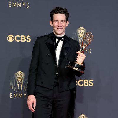 Josh O'Connor, klädd i svart kostym och vit skjorta, poserar med sin Emmystatyett framför en svart vägg. Han ler och tittar in i kameran.